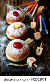 Tasty donuts with jam on wooden background - Hanukkah celebration concept
