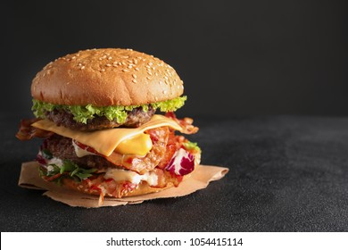 Tasty double burger with bacon on table against dark background