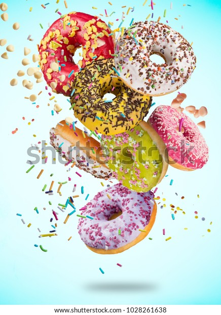 Tasty doughnuts in motion falling on pastel blue background, close-up.