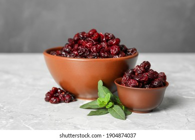 Tasty dried cranberries and leaves in bowls on grey table