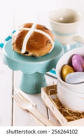 Tasty Easter cross-bun served on a cupcake stand on white wooden background