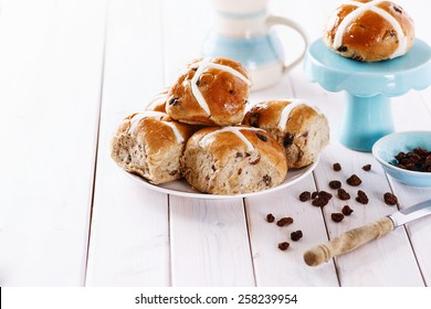 Tasty Easter cross-buns served on a white plate on white wooden background with Copy space. Selective focus, shallow depth of field