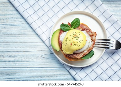 Tasty egg Benedict on plate, top view