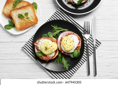 Tasty eggs Benedict on plate, top view