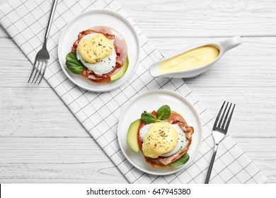 Tasty eggs Benedict on plates, top view