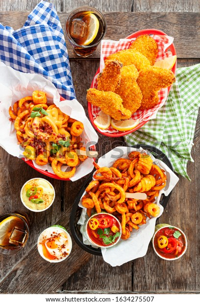 Tasty fast food with curly fries and fried chicken fingers