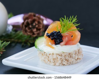 Tasty finger food with smoked salmon and caviar, closeup on white tray over dark background