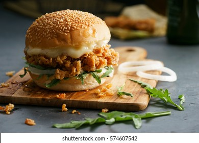 Tasty fired chicken with arugula and mayonnaise sauce served on wooden board
