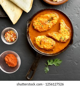 Tasty fish curry in pan on black stone table. Indian style food. Top view, flat lay