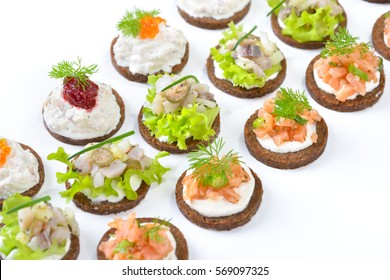 Tasty fish snacks with smoked salmon tartar, trout mousse with caviar and herring salad on pumpernickel bread