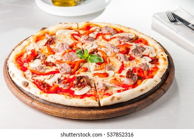 Tasty, flavorful Pizza with veal and mushrooms on the wooden board on the served restaurant table