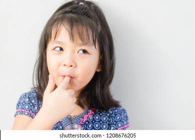 Tasty food and Delicious food concept.Portrait of funny lovely little asian girl put finger into mouth.Beautiful female child girl is showing delicious sign on white background.