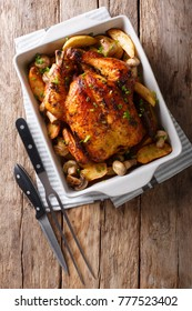 Tasty food: grilled chicken with mushrooms and potatoes close-up in a baking dish on a table. vertical top view from above