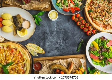 Tasty food on dark table. Grilled pork ribs, pizza, salads, fish and sausages with fried potatoes. Flat lay. Top view. Food frame, restaurant concept.