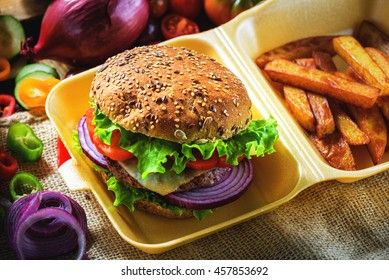 Tasty and fragrant hamburger meat in a healthy integral bread. With the fresh tomatoes, onion and lettuce with the addition of fried chips.