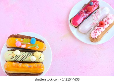 Tasty French eclairs with icing, cream, fresh berries and sugar decor elements. Set of delicious eclairs with creative colorful decor on white plates on the pink textured table. Homemade profiteroles