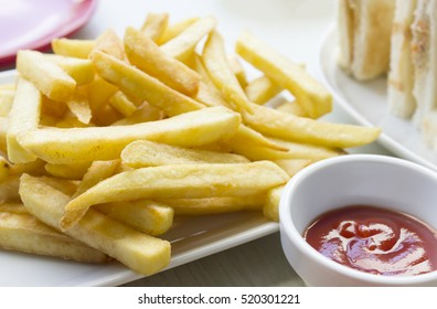 Tasty french fries in dish with tomato sauce on wooden table background.