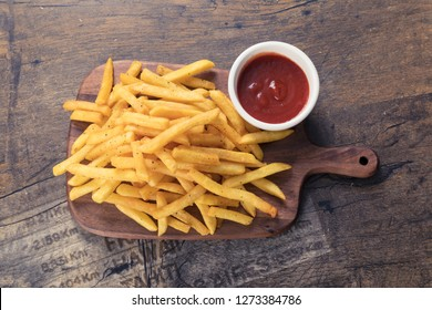 Tasty french fries on cutting board, on wooden table background - Image