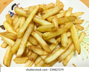 Tasty french fries on wooden table background. art