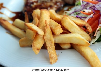Tasty french fries in white dish of steak and salad.