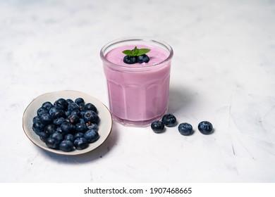 Tasty fresh blueberry yoghurt shake dessert in glass standing on white table background. Homemade berry smoothie. Healthy eating. Diet food yogurt