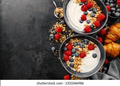 Tasty fresh breakfast with yogurt, granola and fruits served in bowl. Dark background. Closeup.
