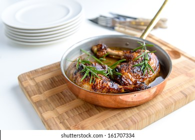 Tasty fresh Chicken bone in a copper pan with some herbs on the side