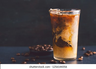 Tasty fresh cold iced coffee with milk in tall glass on table. Horizontal with copy space.