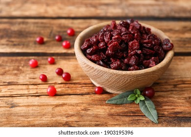 Tasty fresh and dried cranberries with leaves on wooden table