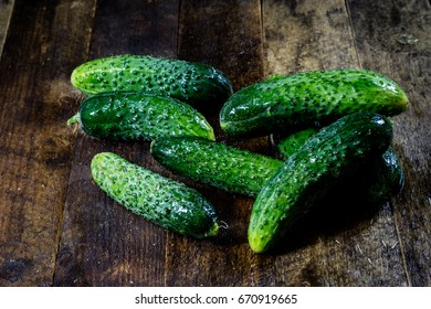 Tasty and fresh ground cucumbers on a wooden kitchen table, black background.