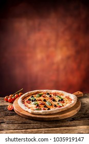 Tasty fresh italian pizza served on old wooden table.