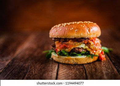 Tasty fresh meat burger with cheese, tomato, onion, avocado, bacon and tomato sauce served on wooden table