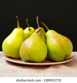 Tasty fresh pears on pink plate, side view. Closeup.
