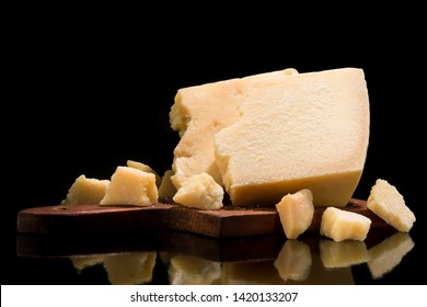 Tasty and fresh pieces of Parmesan cheese on a partitioning wooden board, black background.