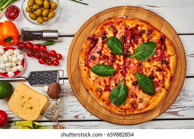Tasty fresh pizza with basil. Composition from baked pizza and fresh vegetables.