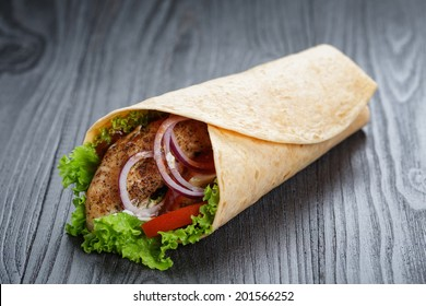 tasty fresh wrap sandwich with chicken and vegetables, on wood table