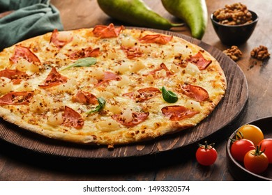 Tasty freshly prepared pizza with pear, nuts and bacon on a wooden board, rustic style.