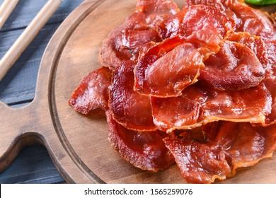 Tasty fried bacon on wooden board