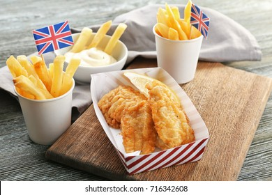 Tasty fried fish and potato chips on wooden table
