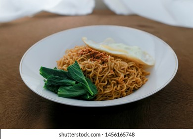 Tasty Fried noodle (Indomie Goreng) with sunny side up egg, and vegetable. served on white plate. Top view close up detail