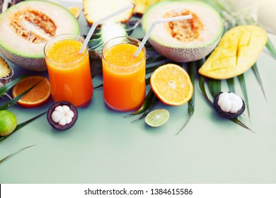 Tasty fruits and multy fruit juice over pastel color background with palm leaves