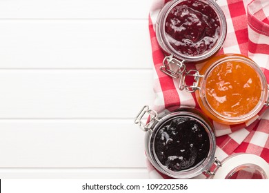 Tasty fruity jam in jar on white table.