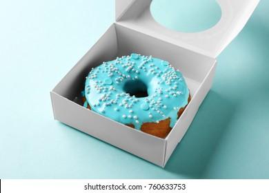 Tasty glazed donut in box on color background