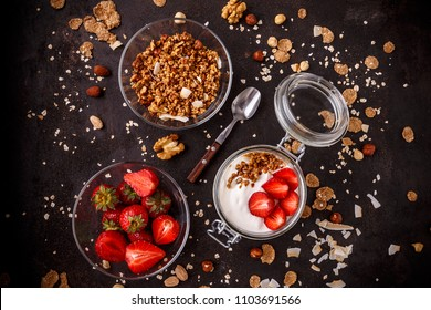 Tasty granola with yogurt and fresh strawberries on black background