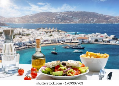 Tasty Greek food with salad, feta cheese and olive oil served with a view to the beautiful island of Mykonos, Greece, during summer time