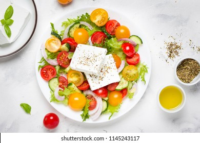 Tasty greek salad with colorful cherry tomatoes red and yellow, cucumber, onion, lettuce and large piece of feta cheese with herbs. In white plate on light background