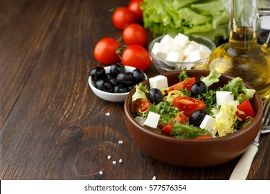 Tasty greek salad with feta, olives and tomatoes in a bowl on wooden background. Copy space for text.