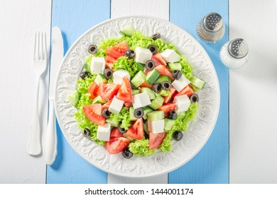 Tasty Greek salad with lettuce, tomatoes and onion