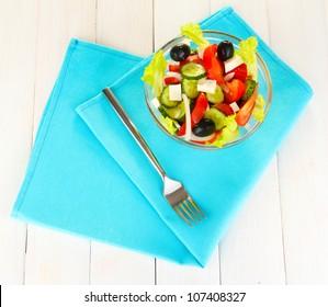 tasty Greek salad on white wooden background