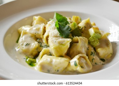Tasty green ravioli and agnolotti with pesto sauce